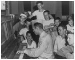 Private Woodall playing the piano for a group of children
