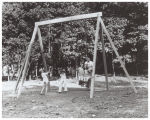 Children playing on swings at Gamble Valley Trailer Park playground