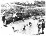 Children play in a swimming hole near East Drive