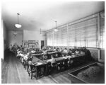 Children sit at tables in a classroom