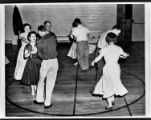 Men and women square dance