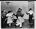 Square dancers dance in a gymnasium