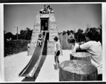 Children climb and play on a sliding board
