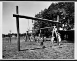 Children play on swings at a playground