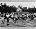 Children ride bicycles in a parade near Chapel on the Hill