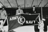 "General Groves and other men hold the Army-Navy ""E"" Award flag"
