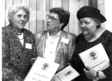 Three women hold a book about local artists